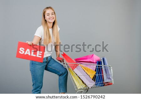 smiling happy blonde woman with sale sign and pushcart with colorful shopping bags isolated over grey