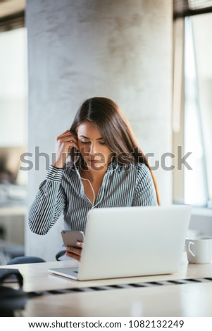 Smiling happy businesswoman with headphones sits at desk, looks at laptop screen, having video call. Young business woman having video call. Pretty woman working on her lap top with headphones on.