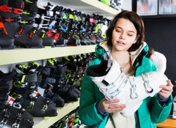 Smiling happy cheerful young female looking for new ski boots in ski equipment shop