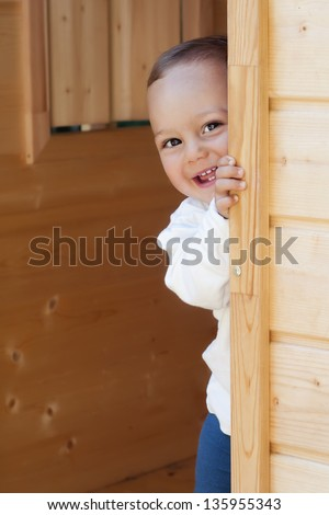 Smiling happy child playing with a door in a wooden playhouse or a small garden shed.