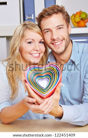 Smiling happy couple holding many colorful hearts in a living room