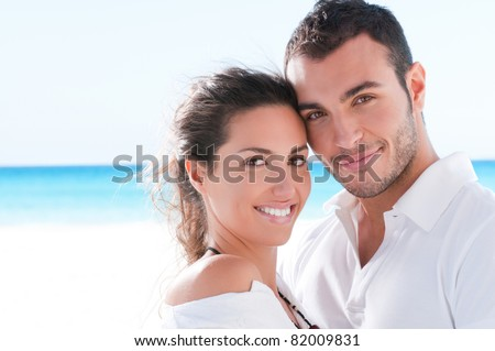Smiling happy couple looking at camera together at summer beach