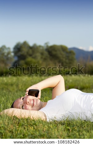 Smiling happy cute girl lying on the grass and talking on tablet phone