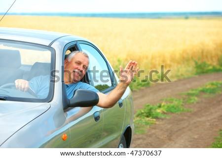 Smiling happy elderly senior  man  in the new car