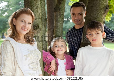 smiling happy family of four outdoors