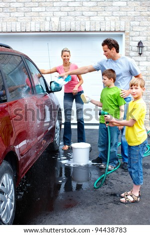 Smiling happy family washing the family car.