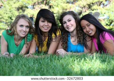 Smiling Happy girl friends in the park with colorful shirts - stock photo