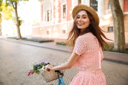 Smiling happy girl in dress and hat riding retro bicycle on a city street and looking at camera