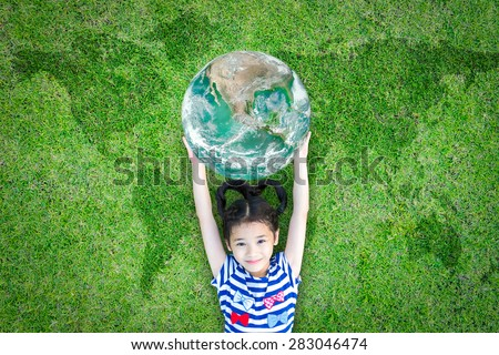 Smiling happy healthy little asian kid holding green globe lying on world global map grass: World environment day CSR concept saving eco green sustainable ecosystem: Element of image furnished by NASA