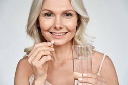Smiling happy healthy middle aged 50s woman holding glass of water taking dietary supplement vitamin pink pill isolated on white background. Old women multivitamins antioxidants for anti age beauty.