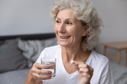 Smiling happy healthy senior woman wake up sits on bed in bedroom alone holding glass of natural water taking daily pill for good health and senile disease prevention, memory meds, vitamins concept