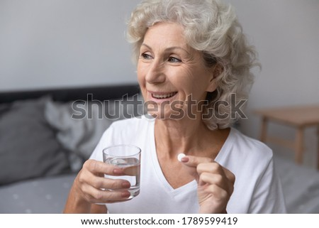Photo of  Smiling happy healthy senior woman wake up sits on bed in bedroom alone holding glass of natural water taking daily pill for good health and senile disease prevention, memory meds, vitamins concept