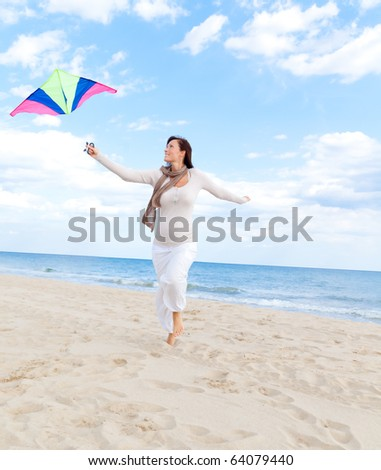 Smiling happy healthy woman walking on beach with kite in winter autumn spring time