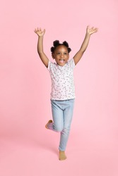 Smiling happy little african american kid girl 6-7 years old wearing casual clothes, standing with hands raised up, looking away and isolated on pink background. Childhood lifestyle concept
