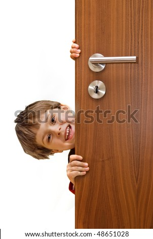 smiling happy little boy looking over door