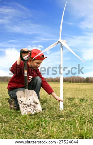 Smiling happy little boy with small windmill and spade. He is planting small windmills on green meadow by spring.