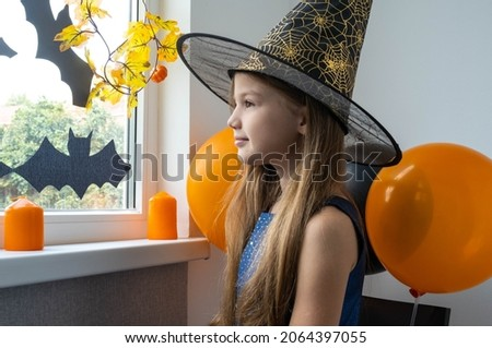 Smiling happy little girl in witch costume preparing for Halloween party at home. Holiday decoration concept.