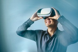 Smiling happy man wearing a Virtual Reality headset as he reacts to a new digitally simulated environment with light flare and an ethereal atmospheric background