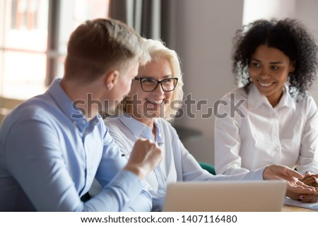 Smiling happy mature older female mentor coach boss executive talking at diverse group meeting having fun business conversation joke laughing with colleagues at corporate team briefing conference