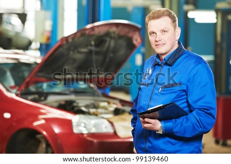 Smiling happy mechanic technician inspector foreman with clipboard at car maintenance repair service station