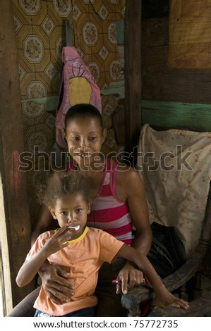 smiling happy mother child daughter inside interior clapboard  house Big Corn Island Nicaragua Central America