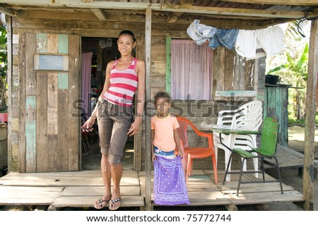 smiling happy mother daughter   porch in front of clapboard house in   Big Corn Island Nicaragua Central America