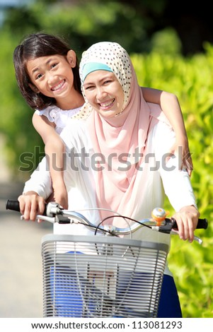smiling happy mother with her daughter riding bicycle
