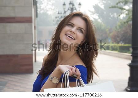 Smiling happy woman carrying shopping bags. Caucasian young woman shopper - stock photo