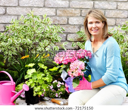 Smiling happy woman gardening near the home