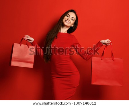 Smiling happy woman in red tight dress holds two red shopping bags and holds lips like in a kiss on red background Stock photo ©