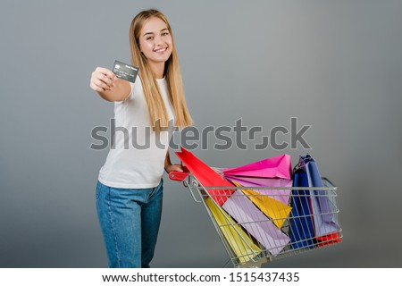 smiling happy woman with credit card  and pushcart full of colorful shopping bags isolated over grey