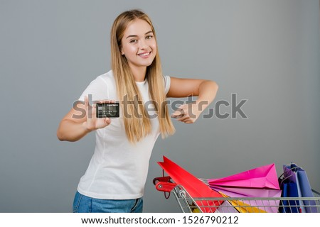 smiling happy woman with credit card and pushcart with colorful shopping bags isolated over grey