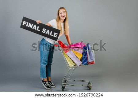 smiling happy woman with final sale sign and pushcart with colorful shopping bags isolated over grey
