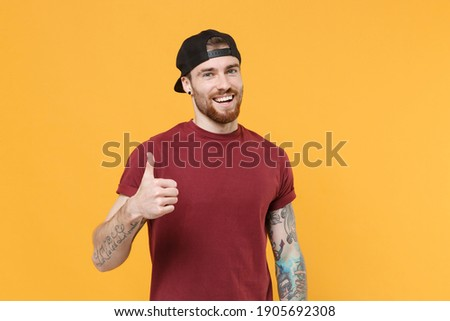 Smiling happy young bearded tattooed man 20s in casual t-shirt, black cap posing showing thumb up isolated on yellow wall background studio portrait. Mock up copy space. Tattoo translate life is fight