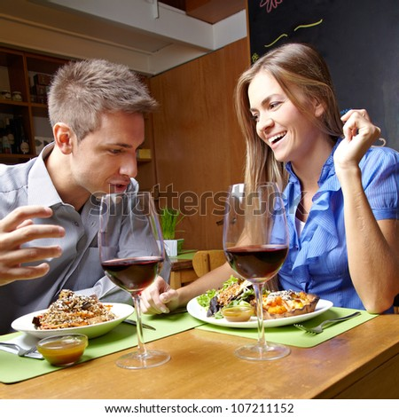 Smiling happy young couple eating in a restaurant