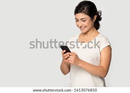 Smiling happy young indian ethnicity lady standing on right, aside blank empty free copy space for advertising text, looking at mobile phone screen, receiving good offer isolated on grey background.