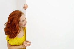 Smiling happy young redhead woman looking at a blank white sign with copy space that she is holding peering around the side with a beaming smile
