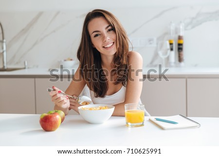 Smiling healthy woman eating corn flakes cereal while sitting and having breakfast at the kitchen table #710625991