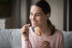 Smiling healthy young woman holding pill glass of water sit on sofa at home, positive lady take daily medicine antioxidant diet vitamin supplements for beauty skin hair health care medicament concept