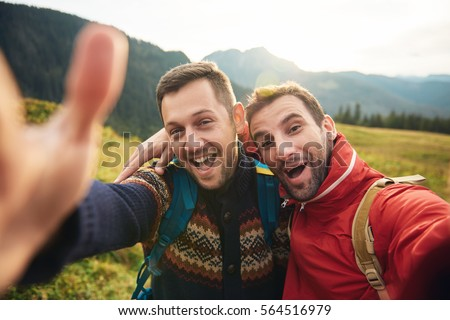 Smiling hikers taking a selfie while trekking in the wilderness