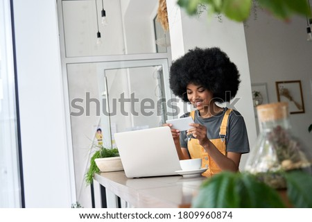 Smiling hipster African American female student using laptop, holding phone watching mobile streaming ad, tv webinar, remote learning, video calling on smartphone sitting alone at table in cozy cafe.