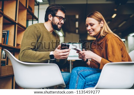 Smiling hipster girl and guy holding mobile phone in hands laughing at funny message, positive couple chatting and checking notification about good news on smartphone connected to 4g internet