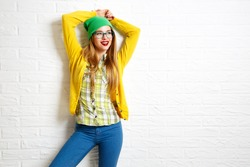 Smiling Hipster Girl at White Brick Wall Background. Street Syle. Trendy Casual Fashion Outfit in Spring or Autumn. Copy Space.