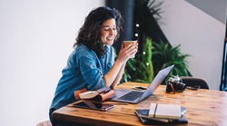 Smiling hipster girl in casual clothing watching positive video on website using laptop computer connected to wifi, cheerful female freelancer enjoying caffeine beverage while working remotely