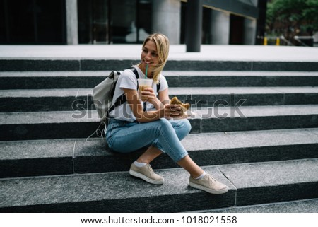 Smiling hipster girl resting on stairs enjoying eating street food on lunch, happy female traveler tasting snack and drinking ice coffee sitting on urban setting having break during walking city trip