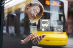 Smiling hipster girl waiting for public transport on bus stop while using application on smartphone for checking train schedule. Infographic illustration bus sign. Female chatting on cellular