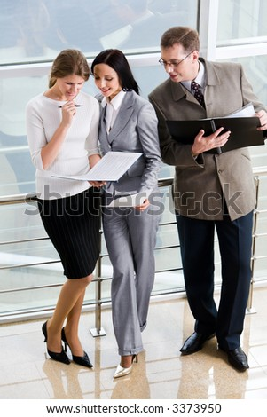 Smiling Hispanic businesswoman giving advices to her colleague and curious businessman in eyeglasses with opened paper case in his hands
