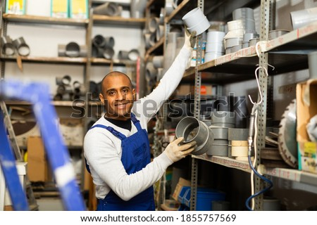 Smiling hispanic foreman looking for PVC pipes and fittings for plumbing works in building hypermarket ストックフォト ©