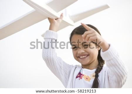 Smiling Hispanic girl playing with toy model plane