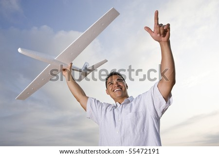 Smiling Hispanic man holding model airplane glider over head